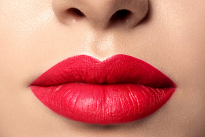 Close up view of beautiful woman lips with red lipstick. Fashion make up. Cosmetology, drugstore or fashion makeup concept. Studio shot