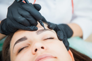 Young woman on permanent make-up procedure, tattooing eyebrows in natural tint. Eyebrow Correction closeup. Beauty Concept.