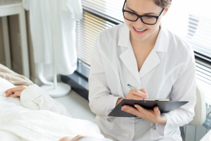 Friendly young beautician wearing white coat and eyeglasses sitting in front of her female client, asking her about intolerance to some medication and taking notes before starting treatment